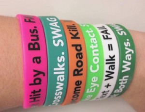 Image of wrist with many braclets with safety messages on them.