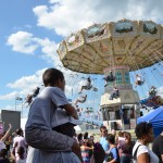 A child watches a ride from his father's shoulders