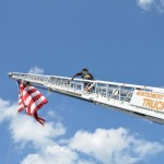 A lone firefighter ascends the ladder above the Fair