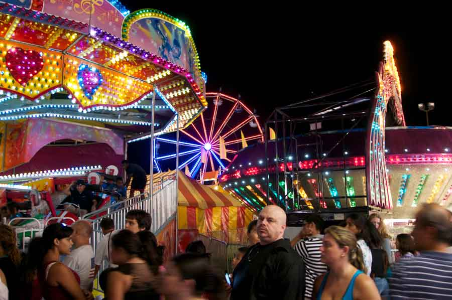 image of Night at the Fair. Bright lights attracted large crowds on the mid-way.