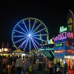 Image of Fair rides and ferris wheel at night