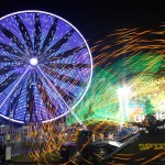 Image of ferris wheel and fair rides at night that looks like sparks
