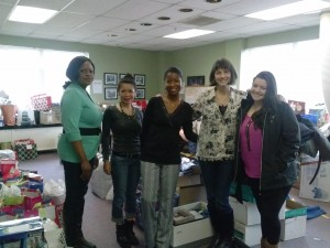 Volunteers from Homes and Hearts for Youth organize gifts donated for children in need.