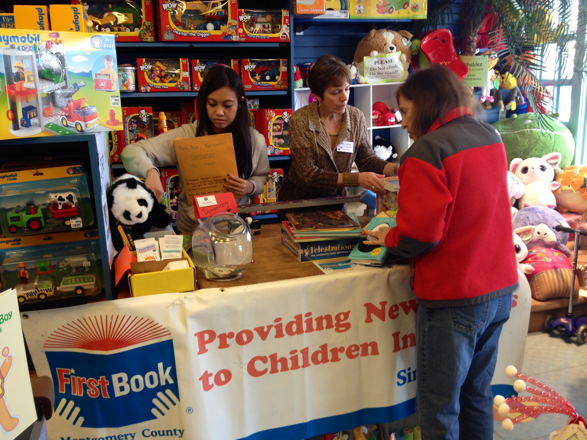 """Volunteers wrap gifts on """"Giving Tuesday"""" for customers at Barston's Child's Play in Rockville."""