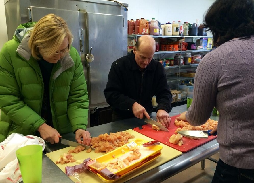 """Members of """"MoCo Cooking for Good"""" prepare a meal for  a local homeless shelter."""