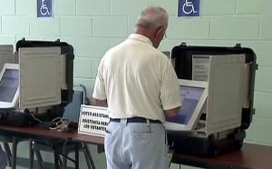 photo of man voting on touchscreen voting machine