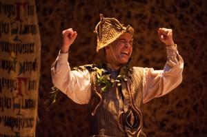 Rumpelstiltskin (Matthew Pauli) cheers with joy when he makes a deal that can't be denied in RUMPELSTILTSKIN at Imagination Stage. Photo | Margot Schulman