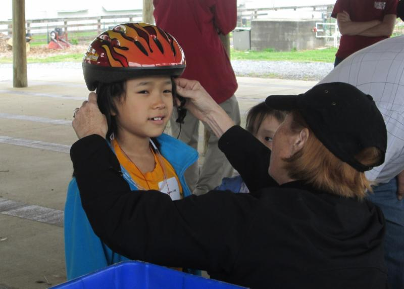 photo of child having bike helmet fitted by woman