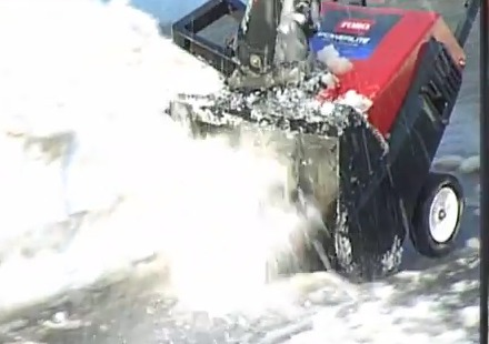person operating snowblower