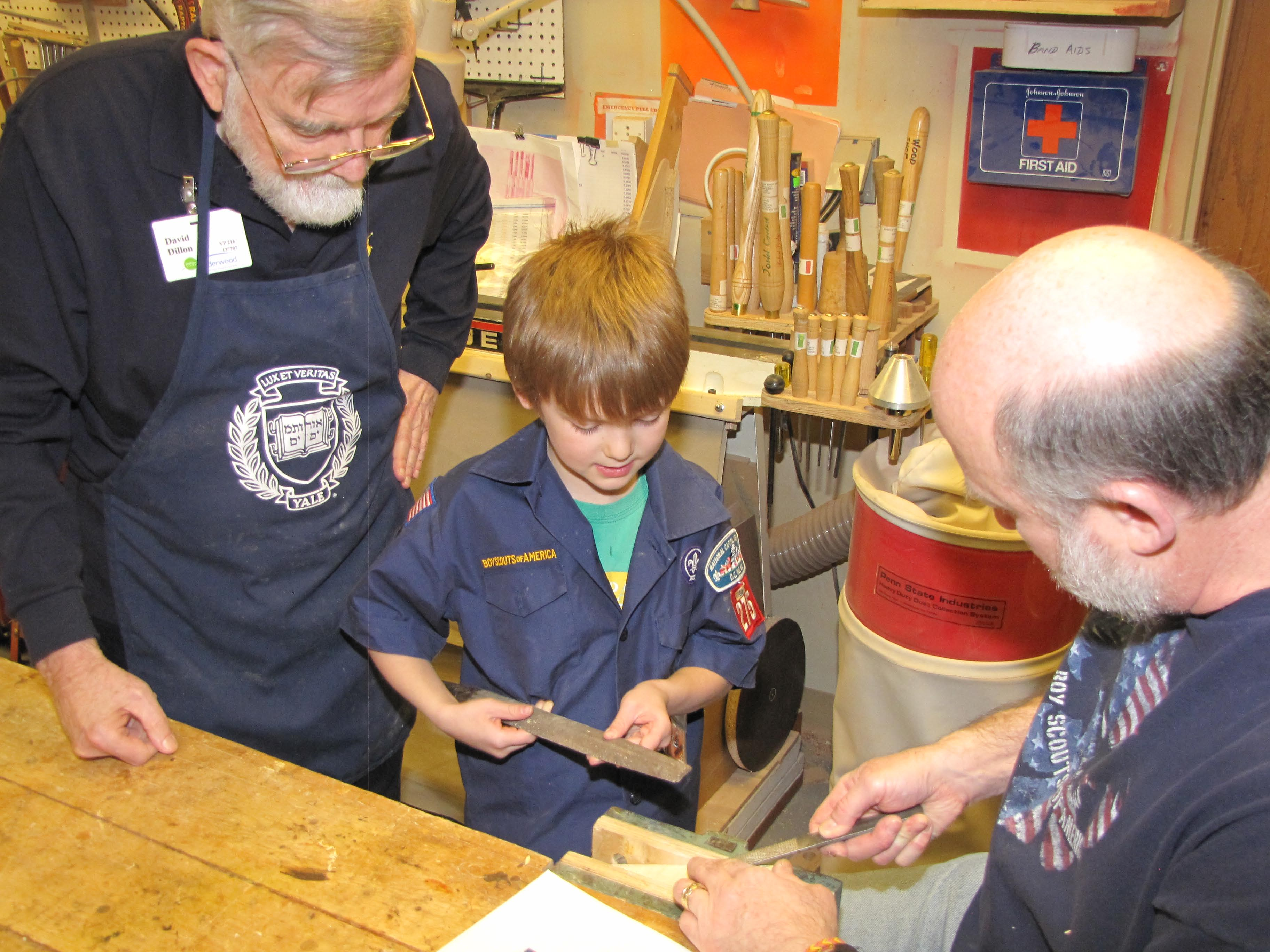 photo of seniors and cub scout working on pine derby in woodshop