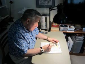 photo of Rev. Jim MacDonell at his drawing board.