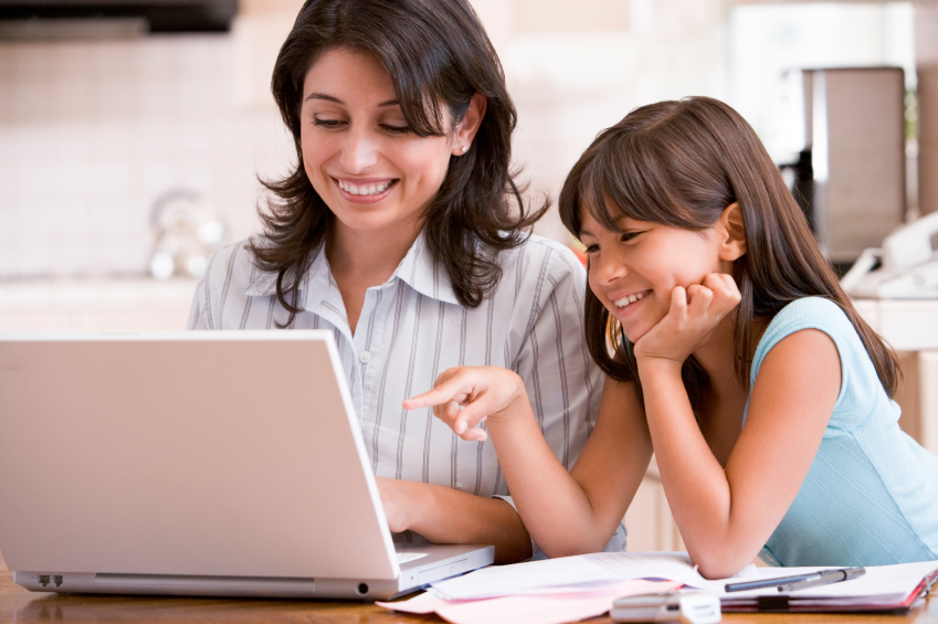 photo of Woman and young girl in kitchen with laptop and paperwork smiling