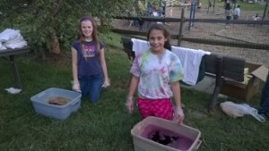 Girl Scout Cadettes Catie, on the left, and Dulce, on the right, at the dye buckets ready to work!
