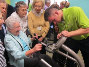 Riderwood, the Erickson Living retirement community in Silver Spring, cut the ribbon on its third fitness center on November 20th.  Beth Trever, a resident, is the first to use the NuStep machine, under the watchful eye of Alvah Tharp, Wellness Coordinator.