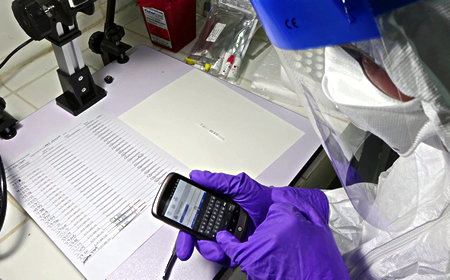 photo of Zalgen lab technician performing tests in protective gear