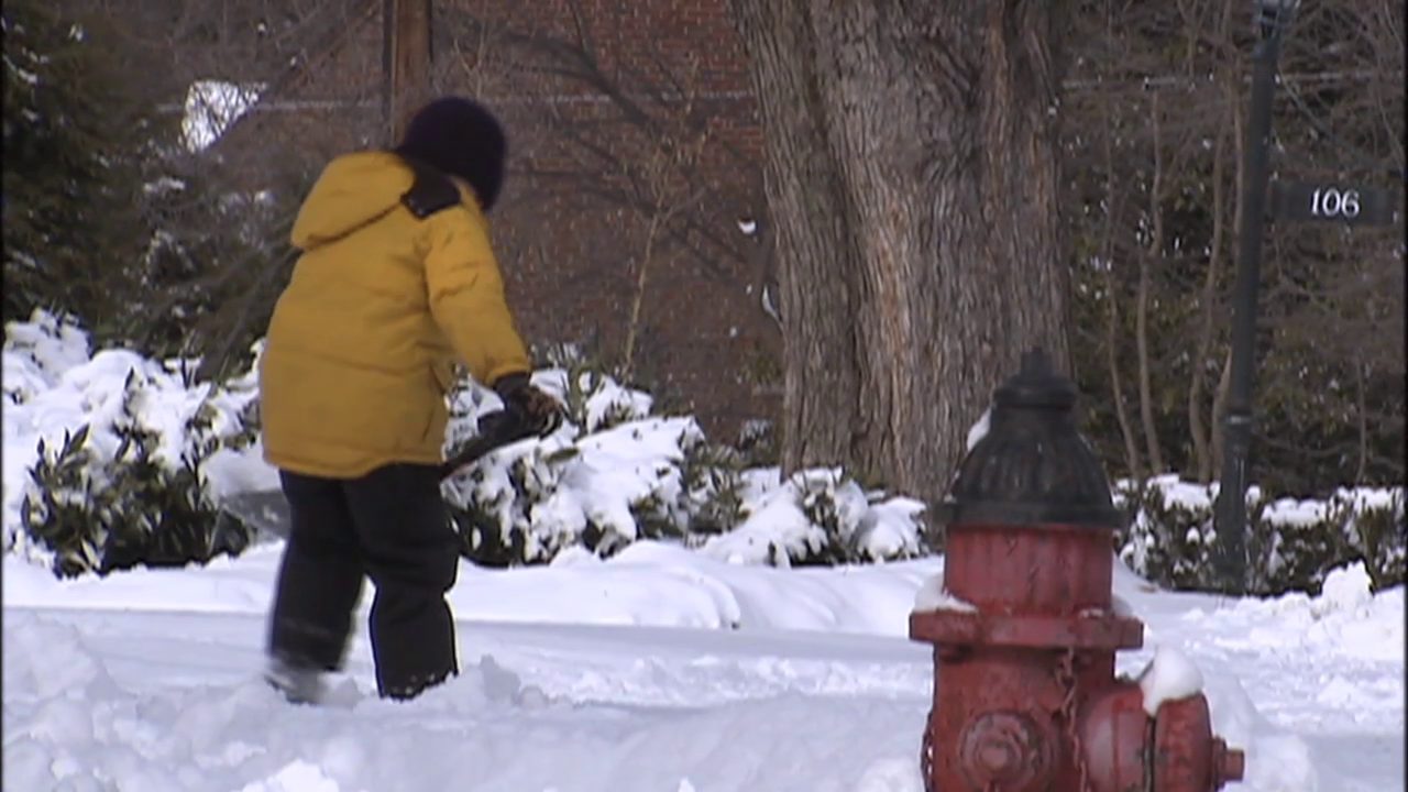 photo of resident shoveling snow from sidewalk after winter storm