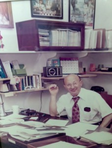 Photo of Harry sitting at desk in office, 1970s