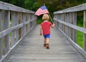 istock Boy carrying American Flag over bridge